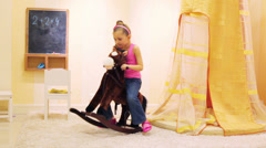 Little girl in jeans and t-shirt swinging on a rocking horse Stock Footage