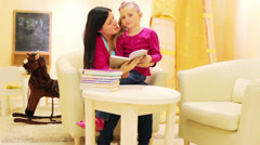 Little girl with her mother reading a book together Stock Footage