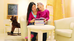 Mother and daughter sitting at the table with a stack of books Stock Footage
