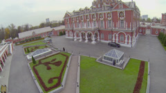 Man in suit walks to edifice of Petrovsky Travelling Palace Stock Footage