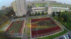 Students play basketball and soccer on playground Stock Footage
