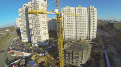 Tall crane works on construction site of residential complex Stock Footage