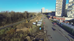 Road traffic near construction site with excavator Stock Footage