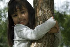 Cute girl in tree - stock photo
