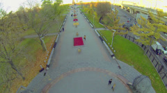 People walk by alley of cosmonauts in park near city street - stock footage