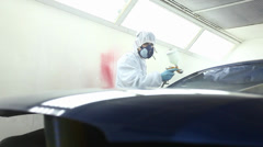 A blue car being varnished in a painting chamber Stock Footage