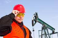 Stock Photo of worker on an oil pump keeps the helmet with his hand