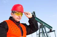 Stock Photo of worker on an oil pump keeps the helmet with his hand,