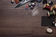 Stock Photo of needles threads and buttons  on brown wooden table