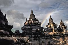 clouds and rainbow buddist temple borobudur complex in yogjakarta in java - stock photo