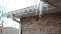 Icicles dripping from roof gutters Stock Footage