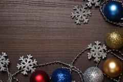 Shiny christmas decoration on brown wooden background Stock Photos
