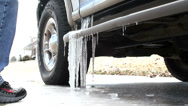 Stock Video Footage of Using foot to break ice off SUV Vehicle