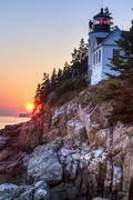Sun setting behind Bass Harbor Lighthouse - stock photo
