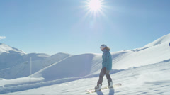 SLOW MOTION: Girl snowboarding on a sunny day Stock Footage