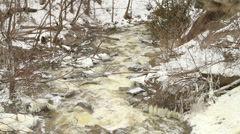Forest creek with rushing water and snowy banks in winter Stock Footage