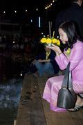 Woman Releasing Krathong in Loi Krathong Festival Stock Photos
