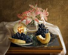 Still life with lily flowers and melon Stock Photos