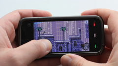 Playing video game on cell phone Stock Footage