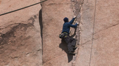 Rock Climber carefully ascends- rope in foreground - stock footage