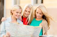 Stock Photo of beautiful women with tourist map in the city