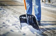 Stock Photo of Man with snow shovel cleans sidewalks in winter