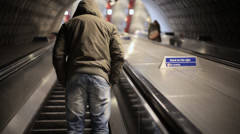 LONDON - waterloo station - Man with hoodie stands on a escalator Stock Footage