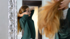 Teenage girl looking in the mirror and touching hair Stock Footage