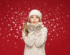 Happy girl in winter clothes blowing on palms Stock Illustration