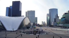 People walk through the Esplanade de la Defense in Paris Stock Footage