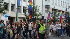 Gay parade crowd marching down the street flags balloons. Stock Footage