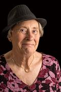 senior lady wearin a fedora with an amused look on her face - stock photo