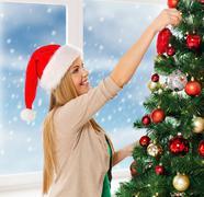 Stock Illustration of woman in santa helper hats decorating a tree