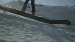 SLOW MOTION: Snowboarder riding down rail Stock Footage