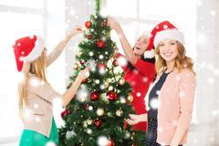 Stock Illustration of women in santa helper hats decorating a tree