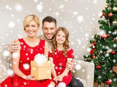 smiling family holding gift box - stock illustration