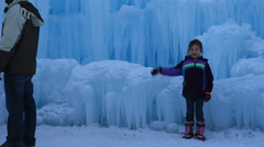 Little girl waving atanding infront of a wall of ice. Stock Footage