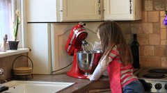 LITTLE GIRL SNEAKING CHOCOLATE CHIPS WHILE BAKING Stock Footage