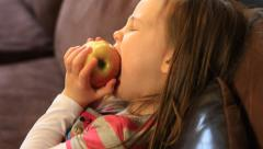 SIDE VIEW PROFILE LITTLE GIRL EATING AN APPLE. Stock Footage