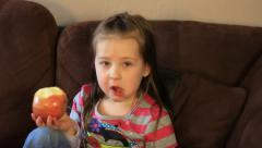 PAN CUTE LITTLE GIRL EATING AN APPLE. Stock Footage