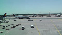 Airport activity on tarmac as seen from lounge - stock footage