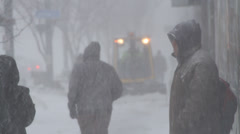 Blizzard in the city, people walking, man waits for a bus, sidewalk plow goes by Stock Footage