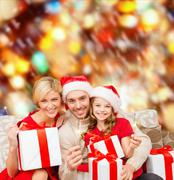 smiling family holding gift boxes and sparkles - stock illustration