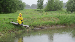 Farmer with waterproof coat on pond bridge feed fishes in rain Stock Footage