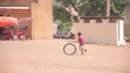 Stock Video Footage of Kid rolling a tyre