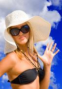 Young beautiful sexy tanned blond woman with hat and bikini laying on sea bea Stock Photos