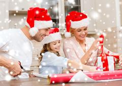 smiling family in santa helper hats with gift box - stock illustration