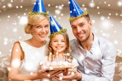 smiling family in blue hats with cake - stock illustration