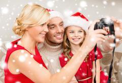smiling family in santa helper hats taking picture - stock illustration