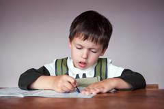 Young boy doing his homework at home - stock photo